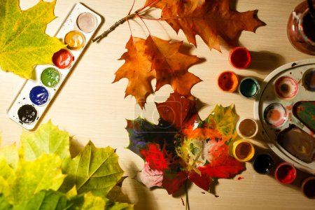 painted with color autumn leaves on table, top view