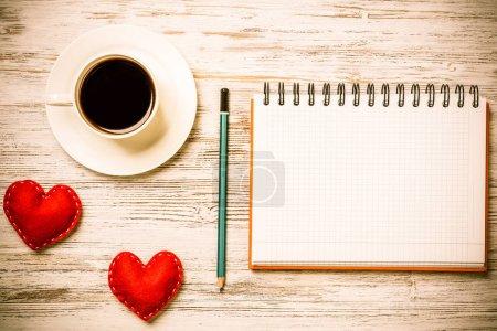 Photo pour Crayon de bloc-notes de tasse à café et deux coeurs rouges sur la surface en bois - image libre de droit