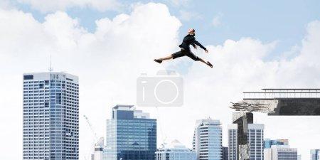Photo pour Femme d'affaires sautant par-dessus un écart énorme de pont en béton comme symbole de surmonter les défis. Paysage urbain sur le fond. rendu 3D. - image libre de droit