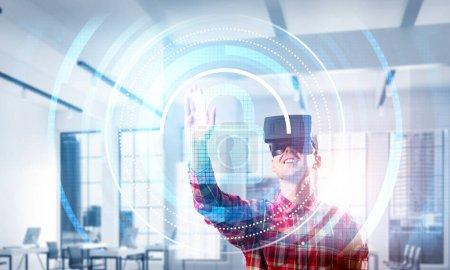 Photo pour Guy portant une chemise à carreaux et un casque virtuel travaillant avec un panneau d'écran multimédia - image libre de droit
