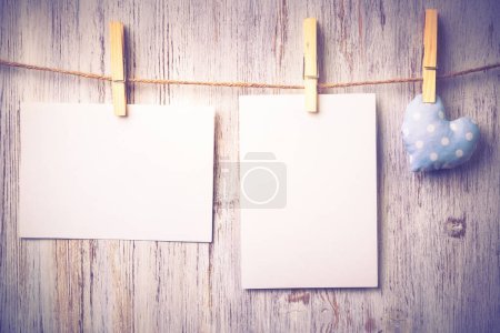 Blank sheets of paper pinned to rope on wooden background