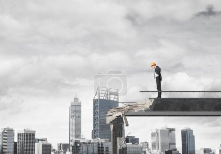 Young engineer in suit and helmet looking down while standing on broken bridge with cityscape on background. 3D rendering.