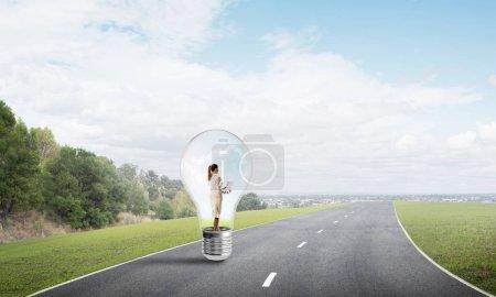 Photo pour Jeune femme d'affaires piégée à l'intérieur de l'ampoule sur la route asphaltée - image libre de droit