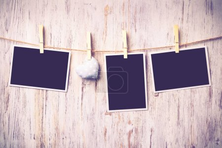 Photo for Instant photo frame and love hearts pinned to rope on wooden textured background - Royalty Free Image