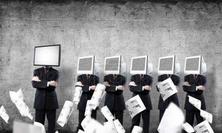 Businessmen in suits with monitors instead of their heads keeping arms crossed while standing in a row and one at the head with TV in empty room against gray wall on background.