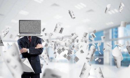 Photo pour Cropped image d'homme d'affaires en costume avec ordinateur portable au lieu de la tête en gardant les bras croisés en se tenant debout entre les papiers à l'intérieur de l'immeuble de bureaux de vol - image libre de droit