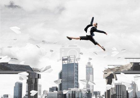 Photo pour Femme d'affaires sautant par-dessus le fossé avec le vol des avions en papier en pont en béton comme symbole de surmonter les défis. Paysage urbain sur le fond. rendu 3D. - image libre de droit