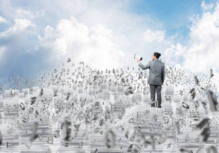 Photo pour Homme d'affaires en costume debout sur une pile de documents parmi des lettres volantes avec haut-parleur à la main avec ciel nuageux sur fond. Techniques mixtes . - image libre de droit