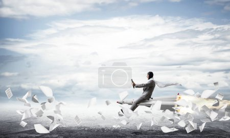 Conceptual image of young businessman in suit flying on rocket above asphalt road and among flying papers with blue sky on background.