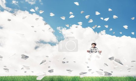 Young little boy keeping eyes closed and looking concentrated while meditating on cloud among flying paper planes with bright and beautiful landscape on background.