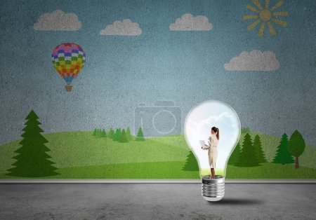 Photo for Businesswoman inside light bulb in room against nature drawn concept - Royalty Free Image