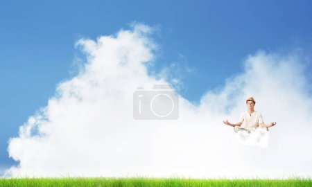 Young man keeping eyes closed and looking concentrated while meditating on cloud in the air with bright and beautiful landscape on background.