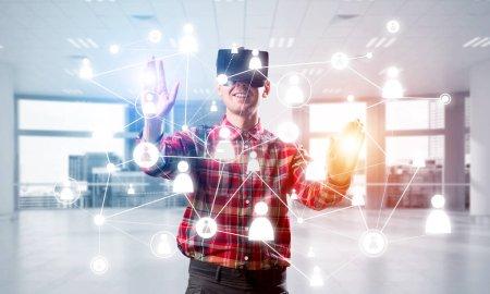 Jeune homme avec casque de réalité virtuelle ou lunettes 3D sur fond de connexion sociale. Techniques mixtes