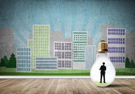 Photo pour Homme d'affaires à l'intérieur ampoule contre la ville concept dessiné - image libre de droit