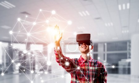 Photo pour Jeune homme avec casque de réalité virtuelle ou lunettes 3D sur fond de connexion. Techniques mixtes - image libre de droit