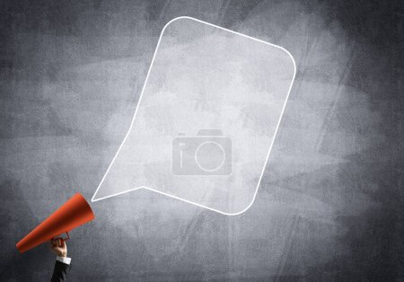 Main de femme d'affaires tenant trompette en papier rouge et nuage de parole