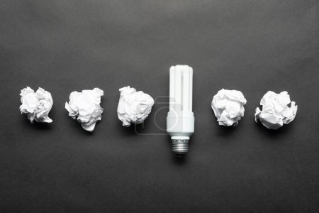 Photo for Fluorescent lamp and crumpled white paper balls on black background. Idea generation and brainstorming motivation. Business concept of successful and failing ideas. Creative and genius solutions - Royalty Free Image