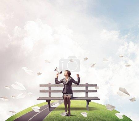 Photo pour Femme d'affaires avec mégaphone sur banc en bois. Haut-parleur féminin criant dans haut-parleur à l'extérieur. Panorama avec horizon rond du monde et avions volants en papier. Marketing d'entreprise et annonce . - image libre de droit