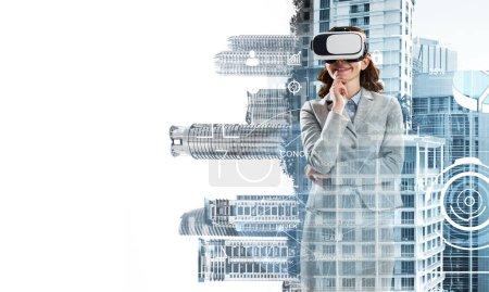 Photo pour Double exposition de femmes d'affaires portant des lunettes de réalité virtuelle et paysage urbain moderne - image libre de droit
