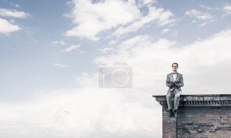 Photo pour Homme drôle en lunettes rouges et costume assis sur le dessus et le livre de lecture - image libre de droit
