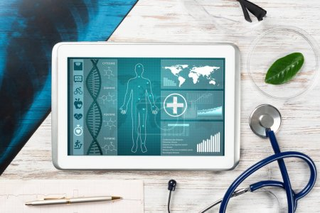 Photo for Human genetic research in medical laboratory. Tablet computer with DNA helix structure on screen. Stethoscope, x-ray image and cardiogram on wooden desk. Medical diagnostics and patient genome testing - Royalty Free Image