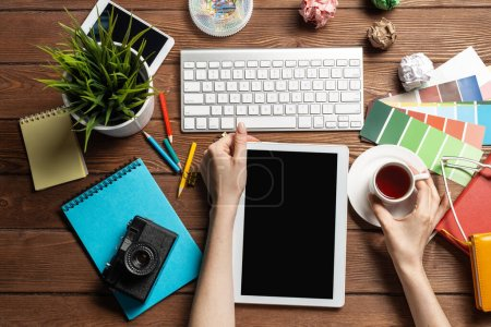 Photo for Freelancer sitting at desk and tablet computer. Business occupation and innovation technology. Home office workspace with camera and cup of coffee. Woman blogger or columnist work at wooden desk. - Royalty Free Image