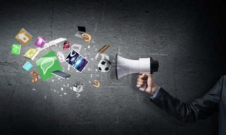 Photo for Businessman hand holding megaphone on wall background. Various things flying out from loudspeaker. Sport competitions announcement and advertisement. Business news broadcasting and online streaming - Royalty Free Image