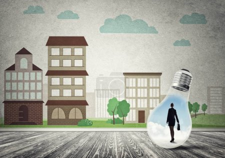 Photo for Businesswoman inside light bulb against city drawn concept - Royalty Free Image