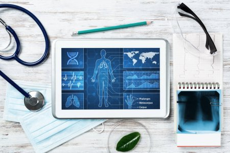Laboratory patient examination in doctors office. Tablet computer with medical app interface on screen. Stethoscope, x-ray image and cardiogram on wooden desk. Medical diagnostics and examination