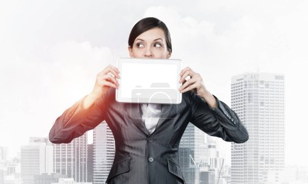 Photo pour Femme d'affaires tenant un ordinateur tablette avec écran blanc. Belle femme en costume d'affaires montre tablette PC près de son visage. Homme d'affaires d'entreprise sur fond de paysage urbain. Présentation de la technologie numérique. - image libre de droit