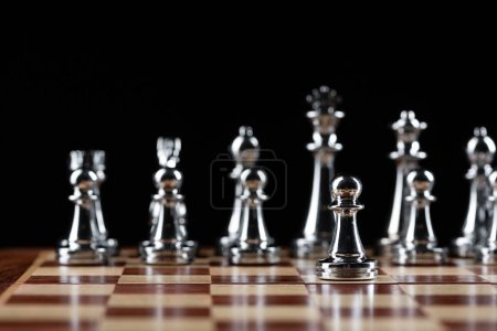 Steel chess figures standing on wooden chessboard....