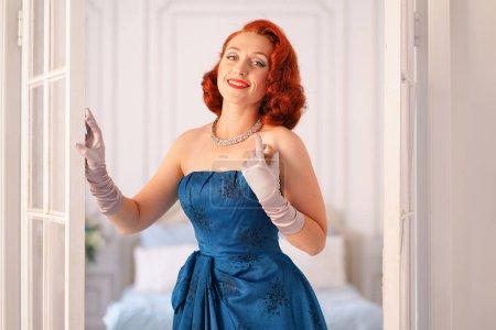 Photo pour Une luxueuse dame pin up vêtue d'une robe vintage bleue se tient à la porte de sa chambre et vous invite à venir à l'intérieur - image libre de droit