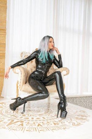 Latex fetish woman wearing black rubber catsuit po...