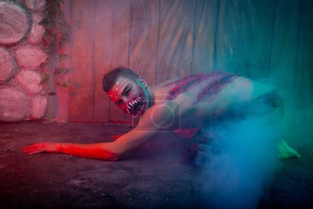 scary vampire male with huge teeth and bloody body as halloween body art standing in the night smoke alone