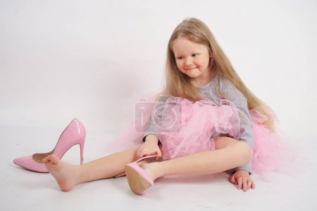 A little caucasian blonde girl sits and puts on he...