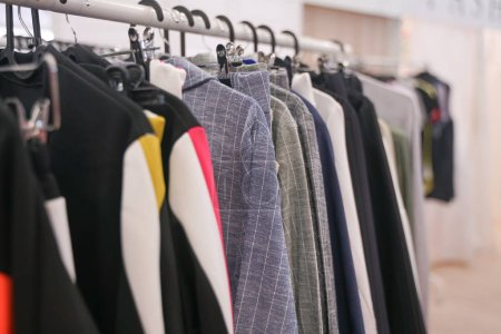 Photo for Fashionable clothes hanging on hangers in the store. nobody. - Royalty Free Image