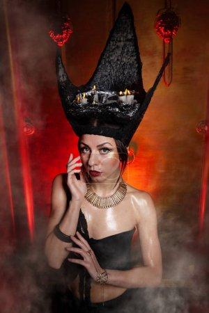 Evil stylish woman witch with big black hat on dar...