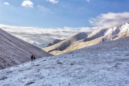 Foto de Kirguistán. Un grupo de turistas en una caminata de montaña recorriendo las pistas con mochilas. - Imagen libre de derechos