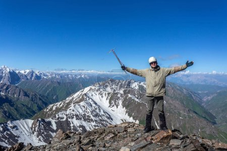 Photo for Summer Kyrgyzstan. Climber on top of a mountain with an ice ax in gear. Climbing in the mountains. - Royalty Free Image
