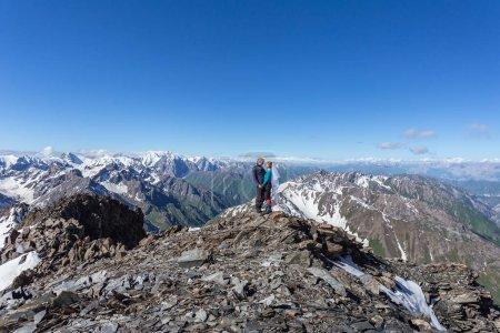 Photo pour Été Kirghizistan. Les alpinistes s'accouplent au sommet d'une montagne avec un piolet à glace en équipement. Escalade en montagne. - image libre de droit