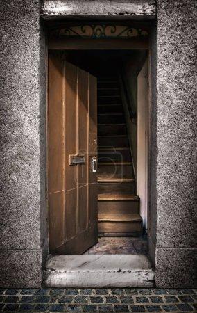 Photo pour Porte moitié ouverte montrant un escalier en bois à l'intérieur d'une vieille maison - image libre de droit