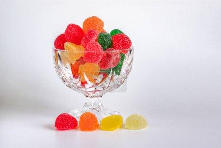 Photo pour Assortiment de bonbons colorés dans un bol en verre sur fond blanc - image libre de droit