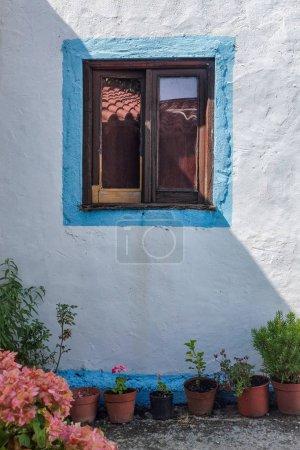 Photo pour Façade de maison rurale avec fenêtre et vieux vases de fleurs - image libre de droit