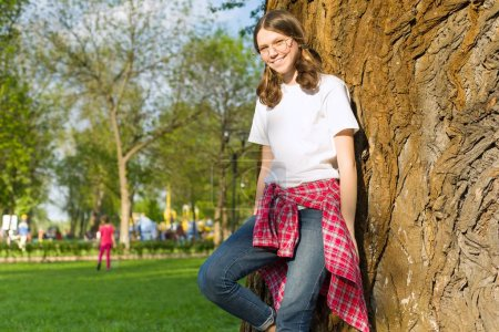 Portrait of teenage girl 13, 14 years old. Female with glasses in casual clothes, smiling, background city park,tree, grass, meadow
