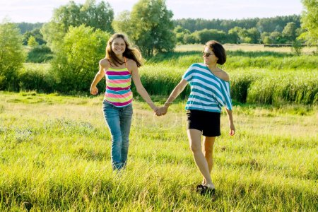 Parent and teenager, Happy mother and teen daughter 13, 14 years old hold hands go laugh talk. Background nature, park