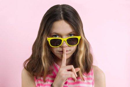 Photo pour Adolescente grave 13,14 ans dans des verres jaunes vives montrent signe de silence, garde avant doigt sur fond de studio de lèvres, rose. Gens, le concept de langage du corps. - image libre de droit