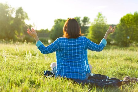 Photo for Woman meditating, practicing yoga in nature, view from the back. Sunset, rustic landscapes, green meadow, - Royalty Free Image