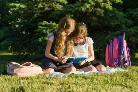 Photo for Two little girl friends schoolgirl learns sitting on a meadow in the park. Children with backpacks, books, notebooks - Royalty Free Image