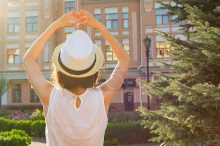 Photo pour Fille dans le chapeau montre le cœur avec ses doigts, se tient avec son dos, regarde le coucher du soleil, fond style ville . - image libre de droit