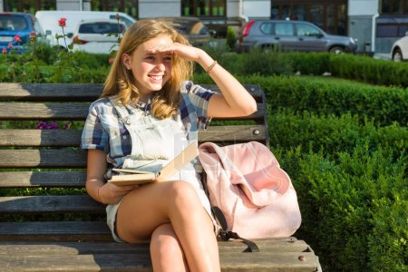 Outdoors portrait of teenage schoolgirl 13, 14 years old sitting on bench in city park with book